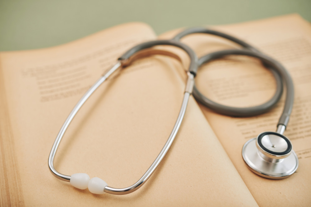 Stethoscope on opened medical book, selective focus